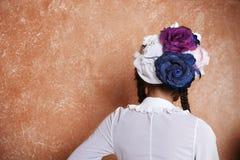 时兴的帽子的女孩由花制成 免版税库存图片