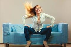 时兴的放松在长沙发的女孩佩带的牛仔布 免版税库存照片