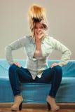 时兴的放松在长沙发的女孩佩带的牛仔布 免版税库存图片