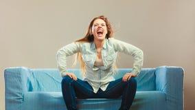 时兴的放松在长沙发的女孩佩带的牛仔布 库存图片