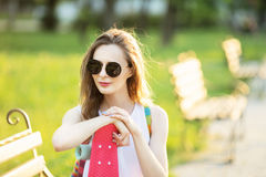 时兴的白肤金发的女孩坐一条长凳在城市公园 库存图片
