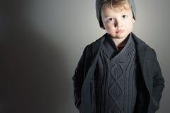 时兴的矮小的Boy.Stylish英俊的孩子。时尚孩子。在衣服、毛线衣和盖帽 免版税库存图片