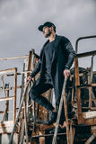 时兴的穿着体面的人画象在金属生锈的楼梯站立 免版税库存照片