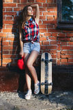 时兴的美丽的少妇画象有滑板的 免版税库存照片