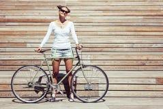 时兴的美丽的年轻俏丽的女孩简而言之和与自行车的T恤杉立场固定在齿轮nex明亮木的板条墙壁  库存照片