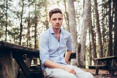 时兴的英俊的人坐长凳在公园野餐区在森林里 免版税库存照片
