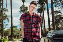 时兴的年轻性感的站立在城市街道上的人佩带的街道样式成套装备在汽车和棕榈附近热的夏日 免版税图库摄影