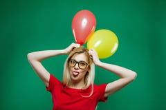 时兴的玻璃的女招待是做鬼脸和看拿着在的照相机黄色和红色气球 图库摄影