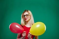 时兴的玻璃的女招待是做鬼脸和看拿着在的照相机黄色和红色气球 免版税图库摄影