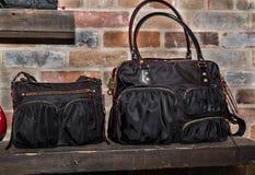 时兴,时髦的妇女黑色袋子,站立在木架子的钱包反对老砖背景 免版税库存照片