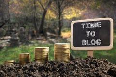 时刻Blog概念 在土壤黑板的金黄硬币在被弄脏的自然本底 免版税库存照片