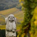昂德洛,阿尔萨斯村庄,葡萄园,修士运载的葡萄酒桶雕象  免版税库存图片