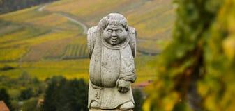 昂德洛,阿尔萨斯村庄,葡萄园,修士运载的葡萄酒桶雕象  库存图片