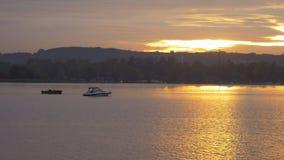 昂贵的小船和便宜的小船在水在美好的日落 在城市之外的休息 晚上天际 不同 股票视频