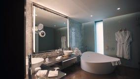 昂贵的卫生间内部,巨大的镜子和木盆,白色毛巾堆