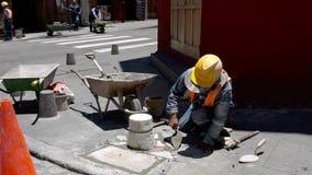 昆卡省,厄瓜多尔- 20180920 -工作者修平刀在边路修理的新的瓦片附近填水泥 股票视频
