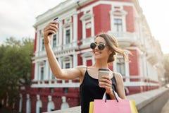 明亮地微笑年轻可爱的女性白种人的女孩画象有黑发的在棕褐色的玻璃和黑礼服 免版税库存图片