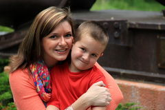 年轻明亮地微笑母亲和的儿子,当他们拥抱时 库存图片