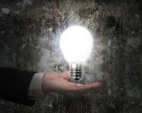 明亮地拿着电灯泡的人的手照亮了黑暗的老墙壁 免版税库存照片
