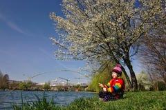 明亮地色的女孩假装钓鱼在一棵开花的树下 库存图片