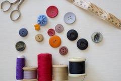 明亮地色的按钮和缝合的棉花 免版税图库摄影