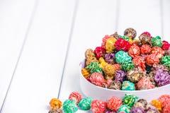 明亮地色的糖煮的玉米花,白色背景 速食,在浅粉红色的碗的水果味道的玉米花的水平的图象 colo 免版税图库摄影