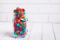 明亮地色的糖煮的玉米花,白色背景 速食,在玻璃瓶子泥工的水果味道的玉米花的水平的图象 colo 免版税库存图片