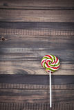 明亮的五颜六色的圆的棒棒糖木背景 免版税库存照片