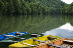 明亮的五颜六色的小船在安静的山湖停泊了 库存图片