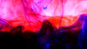 明亮的五颜六色的背景蓝色和红色液体墨水上色混和在水中 免版税库存照片