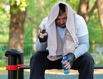 明亮的体育衣裳的一个年轻人有在他的头的一块毛巾和一个瓶的水在他的手上坐健身房公开 图库摄影