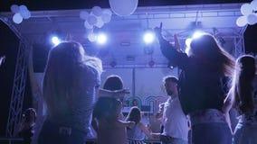 明亮的光的夏天迪斯科,年轻人和女孩在夜总会,与被举的胳膊的青年时期跳舞停留 影视素材