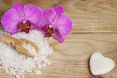 明亮的兰花在白色腌制槽用食盐和一块心形的石头旁边开花在一张木桌上 免版税库存照片