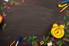 明亮的办公用品,在黑黑板顶视图,拷贝空间的黄色闹钟 概念:回到学校 免版税图库摄影