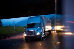 明亮的半卡车在下雨夜中在高速公路点燃 免版税图库摄影