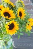明亮的向日葵花束在一个玻璃瓶子的在一张木桌上 库存照片