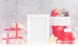 明亮的圣诞节嘲笑与照片框架:欢乐礼物盒、玩具和冷杉锥体在红色圣诞老人` s起动在雪下 免版税库存图片