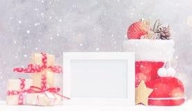 明亮的圣诞节嘲笑与照片框架:欢乐礼物盒、玩具和冷杉锥体在红色圣诞老人` s起动在雪下 免版税图库摄影