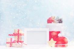 明亮的圣诞节嘲笑与照片框架:欢乐礼物盒、玩具和冷杉锥体在红色圣诞老人` s起动在雪下 新年concep 库存图片
