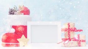 明亮的圣诞节嘲笑与照片框架:欢乐礼物盒、玩具和冷杉锥体在红色圣诞老人` s起动在雪下 图库摄影