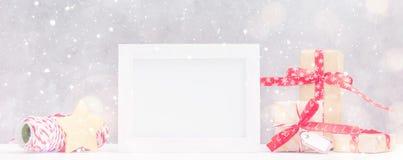 明亮的圣诞节嘲笑与照片框架:欢乐礼物盒,包裹螺纹和金星在雪下 概念新年度 文本sp 免版税库存照片