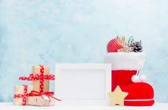 明亮的圣诞节嘲笑与白色水平的照片框架:欢乐礼物盒、玩具和冷杉锥体在红色圣诞老人` s起动 免版税库存照片