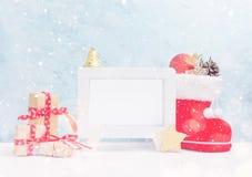 明亮的圣诞节嘲笑与白色照片框架:欢乐礼物盒、玩具和冷杉锥体在红色圣诞老人` s起动在雪下 新年度 免版税库存照片