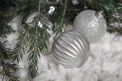 明亮的圣诞节球,一棵圣诞树的分支在雪的 库存图片