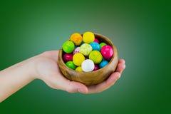 明亮的在一个木碗盘的糖果口香糖在说谎在绿色背景的手掌 免版税库存照片