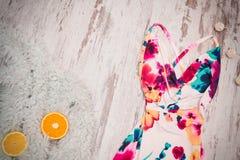 明亮的夏天礼服和桔子在一张灰色虚假毛皮,木背景 时兴的概念,顶视图 库存图片