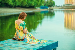 明亮的夏天礼服的红发妇女有开背部的坐在河岸的木码头 免版税库存照片