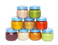 从明亮的多彩多姿的罐头的金字塔用婴儿食品 库存图片