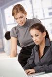 明亮的女实业家办公室运作的年轻人 免版税图库摄影