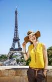 明亮的女衬衫的微笑的妇女反对埃佛尔铁塔在巴黎 免版税图库摄影